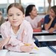 Schoolgirl Leaning On Desk With Students In Background — Stock Photo