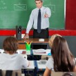 Stock Photo: Teacher Pointing At Students In Classroom