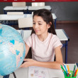 Schoolgirl Searching Places On Globe At Desk — Stock Photo #26652357