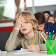 Tired Schoolboy Sitting At Desk In Classroom — Stock Photo