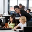 Stock Photo: Female Teacher With Students At Desk