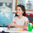 Schoolgirl Searching Places On Globe At Desk - Lizenzfreies Foto
