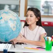 Schoolgirl Searching Places On Globe At Desk — Stock Photo
