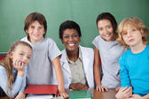 Cute Schoolchildren With Female Teacher At Desk — Stock Photo