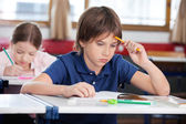 Thoughtful Schoolboy Sitting At Desk — Stock Photo