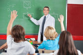 Teacher Teaching While Students Raising Hands — Stock Photo