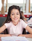 Liseli kızlar sınıfta masada oturan — Stok fotoğraf