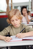 Cute Schoolboy Writing In Book At Desk — Stock Photo