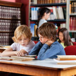 Stock Photo: Schoolboys Reading Book Together In Library