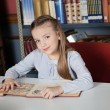 Little Girl Sitting At Table With Books — Foto Stock