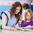 Teacher And Little Girl Reading Book In Classroom — Stock Photo