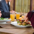 Young Woman Having Burger With Colleagues At Cafe — Stock Photo