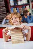 школьник, улыбаясь сидя с стопку книг в библиотеке — Стоковое фото