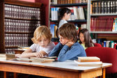 Schoolboys Reading Book Together In Library — Stock Photo