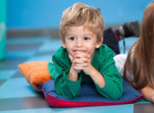 Boy With Hands Clasped Lying On Floor In Kindergarten — Stock Photo