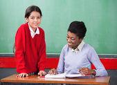 Ciltçi masasında okuma öğretmen ile kız öğrenci portresi — Stok fotoğraf