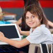 Cute Schoolboy Holding Digital Tablet In Classroom — Stock Photo
