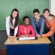Teacher With Teenage Students At Desk In Classroom - Stock Photo