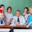 Confident Male Teacher With Schoolchildren  At Desk — Stock Photo