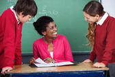 Teacher Discussing With Students At Desk — Stock Photo