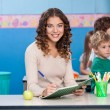 Teacher Writing In Book With Children Playing In Background — Stock Photo #26907637