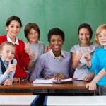 Happy Teacher And Schoolchildren Gesturing Together At Desk — Stock Photo