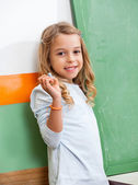 Girl With Chalk Standing By Chalkboard In Class — Stock Photo