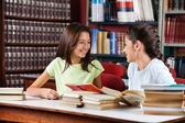 Schoolgirls Looking At Each Other While Studying In Library — Stock Photo
