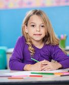 Chica con papel y lápices de dibujo coloreado en el escritorio — Foto de Stock