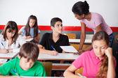 оказание помощи подростка во время обследования в классе учитель — Стоковое фото