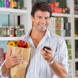 Man With Mobile Phone And Grocery Paper Bag — Stock Photo