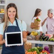 Stock Photo: SaleswomDisplaying Tablet With Customers In Background