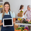 Saleswoman Displaying Tablet With Customers In Background — Stock Photo