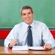 Happy Male Teacher With Pen And Binder Sitting At Desk — Stock Photo #27175557
