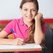 Teenage Schoolgirl Writing At Desk — Stock Photo #27175943