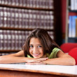Happy Schoolgirl Resting Chin On Hands At Table In Library — Stock Photo