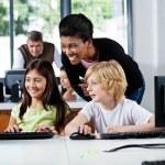 Happy Teacher Assisting Schoolchildren In Using Computer — Stock Photo