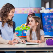 Teacher Teaching Little Girls In Classroom — Stock Photo #27177613