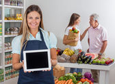 Saleswoman Displaying Tablet With Customers In Background — Stockfoto