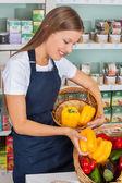 Saleswoman Choosing Bellpeppers In Store — Stock Photo