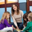 Teacher With Children Reading Book In Classroom — Stock Photo