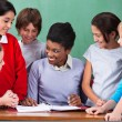 Stock Photo: Happy Teacher Teaching Children At Desk In Classroom