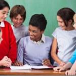 Happy Teacher Teaching Children At Desk In Classroom — Stock Photo