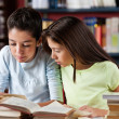 Schoolgirls Reading Book Together In Library — Stock Photo