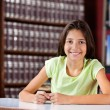 Happy Schoolgirl Sitting In Library — Stock Photo