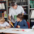 Male Librarian Showing Book To Schoolboy — Stock Photo #27243089