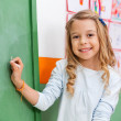 Cute Girl Writing On Board In Kindergarten — Stock Photo