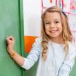 leuk meisje schrijven aan boord in de kleuterschool — Stockfoto #27243447