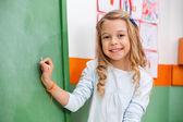 Roztomilá dívka psaní na palubě ve školce — Stock fotografie
