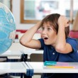 Shocked Schoolboy Looking At Globe In Classroom — Stock Photo